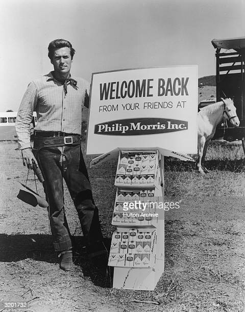 Fulllength portrait of American actor Clint Eastwood posing in Western gear next to a display of Philip Morris tobacco products in front of a white...