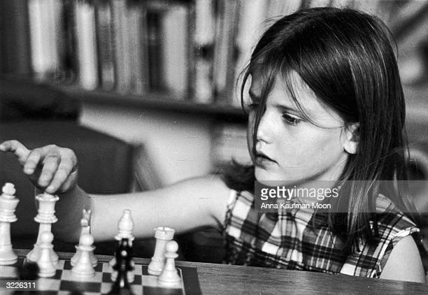 Headshot of a young girl holding her finger on top of the queen chess piece pondering her next move during a chess game A strand of hair hangs in her...