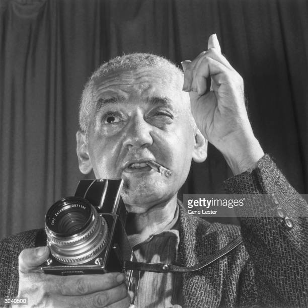 Headshot of Polishborn photojournalist Arthur Fellig known as 'Weegee' holding a camera and pointing his index finger with a cigar in his mouth