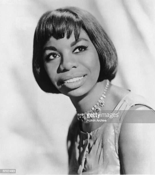 Headshot portrait of American pianist and jazz singer Nina Simone smiling over her shoulder Simone wears a sleeveless dress and a choker