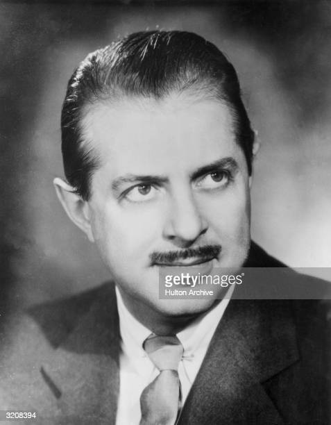 Headshot portrait of American theatrical producer David Merrick smiling while wearing a jacket and tie