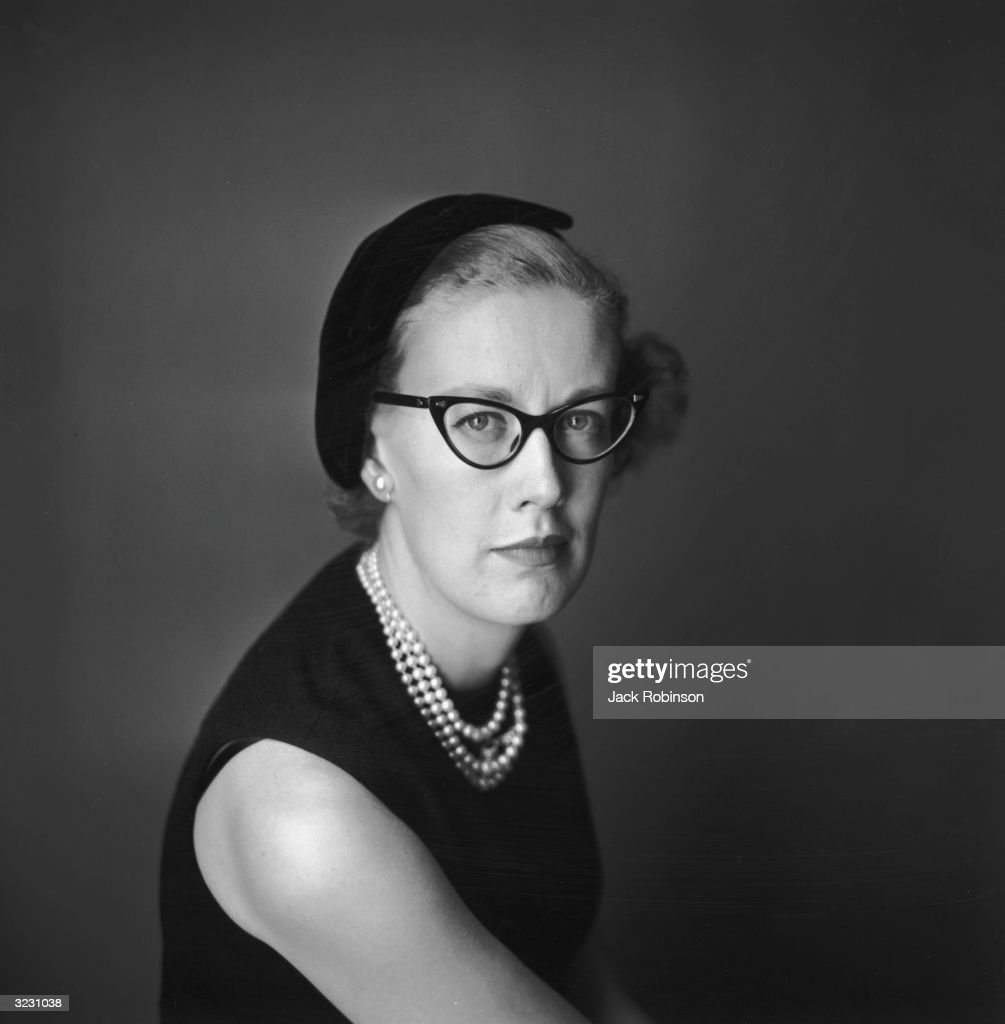 Headshot studio portrait of fashion writer and New York Times editor Carrie Donovan, wearing cats-eye glasses, pearls, and a black cap.