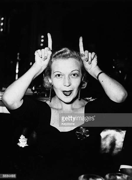 Hungarian actress and singer Martha Eggerth playing the fool and pulling tongues at photographers who are annoying her