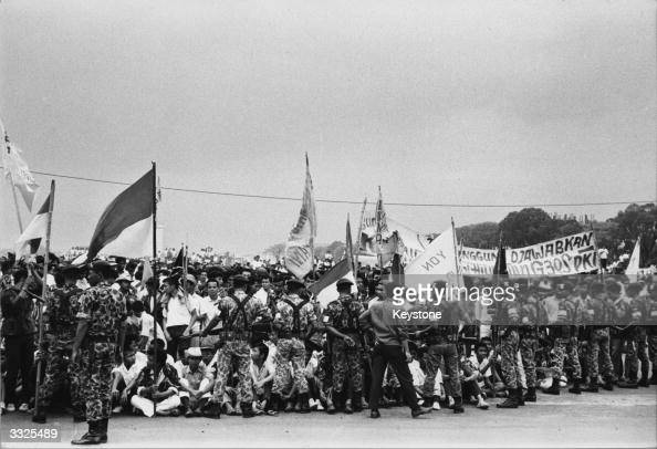 Indonesian troops bar a crowd of flagwaving students from the approach to president Achmed Sukarno's summer palace at Bogor in Indonesia following...