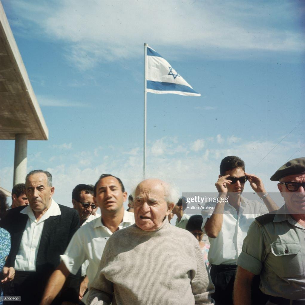 Israel's first prime minister David BenGurion walks amid Israeli citizens and the Israeli flag Israel