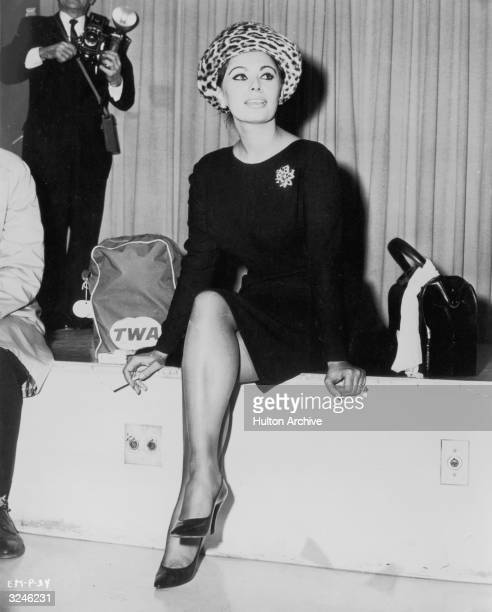 Italian actor Sophia Loren wears a kneelength black dress and leopard print hat while smoking a cigarette in an airport lounge She sits next to a TWA...