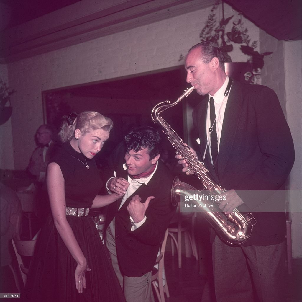 Married American actors Tony Curtis and Janet Leigh dance to the music of a saxophonist. Curtis smiles and points to the musician.
