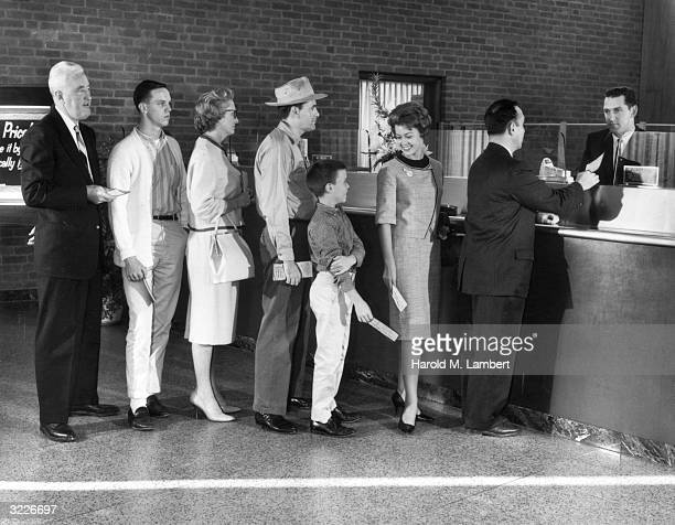 Men women and children stand in a line waiting to see a teller at the bank The teller accepts a slip of paper from a customer
