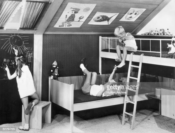 One boy lies on his back in a bed as another boy on a bunk bed looks down at him 1960s A girl draws on a chalkboard next to them The modern bedroom...