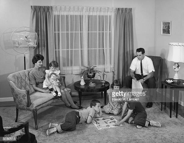 Parents sit in the living room and watch their children play the board game 'Sorry' on the rug The mother holds their youngest daughter who has a...