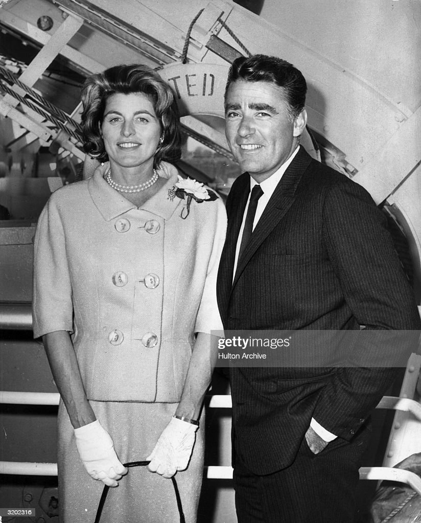 Patricia Kennedy (1924 - 2006) (sister of US president John F. Kennedy) and her husband, British actor <a gi-track='captionPersonalityLinkClicked' href=/galleries/search?phrase=Peter+Lawford&family=editorial&specificpeople=85811 ng-click='$event.stopPropagation()'>Peter Lawford</a> (1923 - 1984), pose together on the gangplank of a ship. Patricia wears a double-breasted blazer and a skirt, with white gloves.