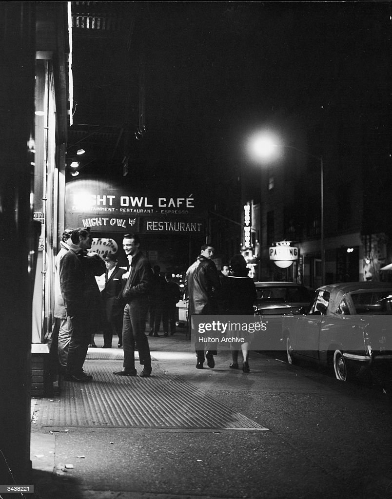 People pass by and stand outside of the Night Owl Cafe in the Greenwich Village neighborhood of New York City