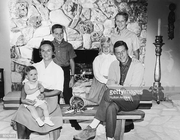 Portrait of American actor and comedian Dick Van Dyke with his wife Margie Willet posing in front of a fire place with their four children Barry...