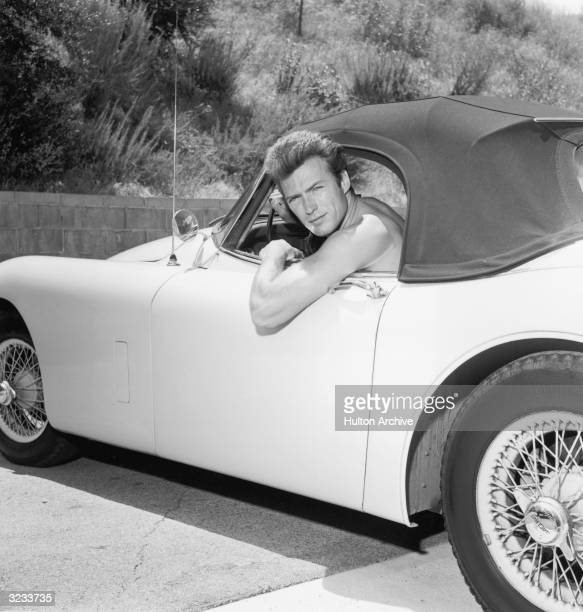 Portrait of American actor Clint Eastwood leaning out the window of a Jaguar convertible without a shirt