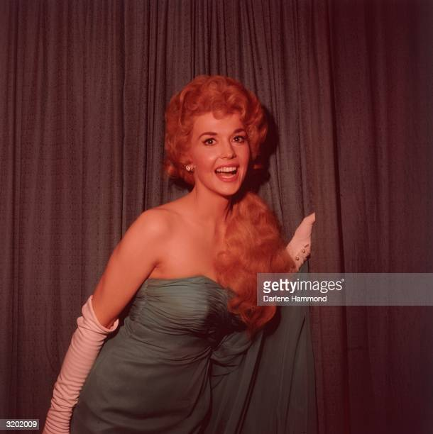 Portrait of American actor Donna Douglas wearing a blue shoulderless gown and long white gloves standing in front of a curtain and smiling