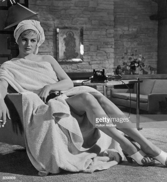 Portrait of Swedishborn actor Anita Ekberg seated with towels wrapped around her togastyle smoking a cigarette with a telephone receiver in her lap...