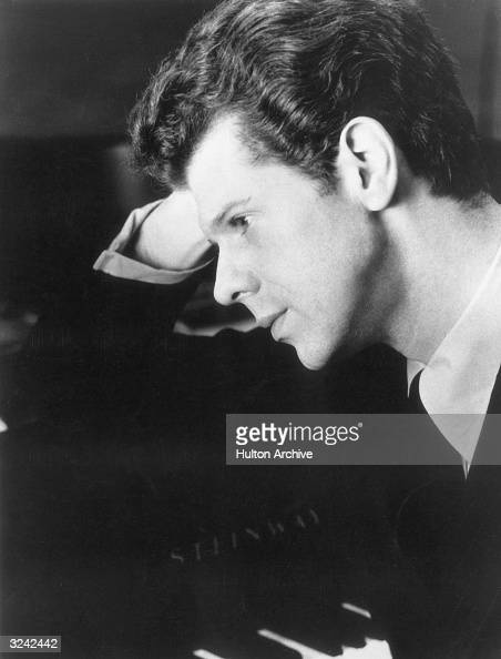 Profile headshot portrait of American pianist Van Cliburn resting his elbow on a piano and leaning his head on his hand