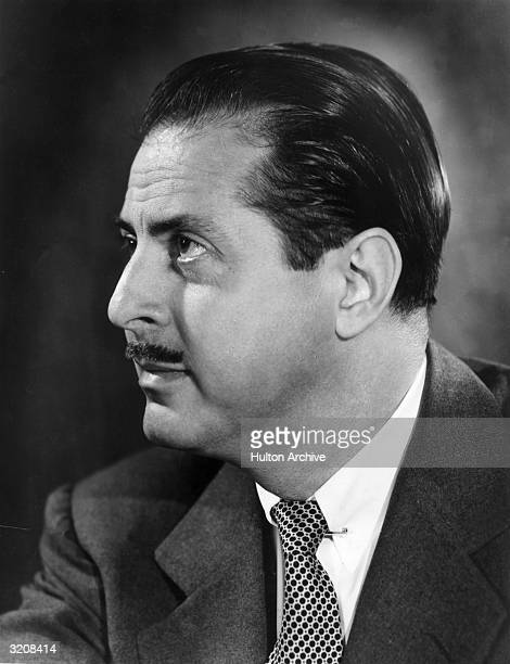 Profile headshot portrait of American theatrical producer David Merrick wearing a jacket and tie