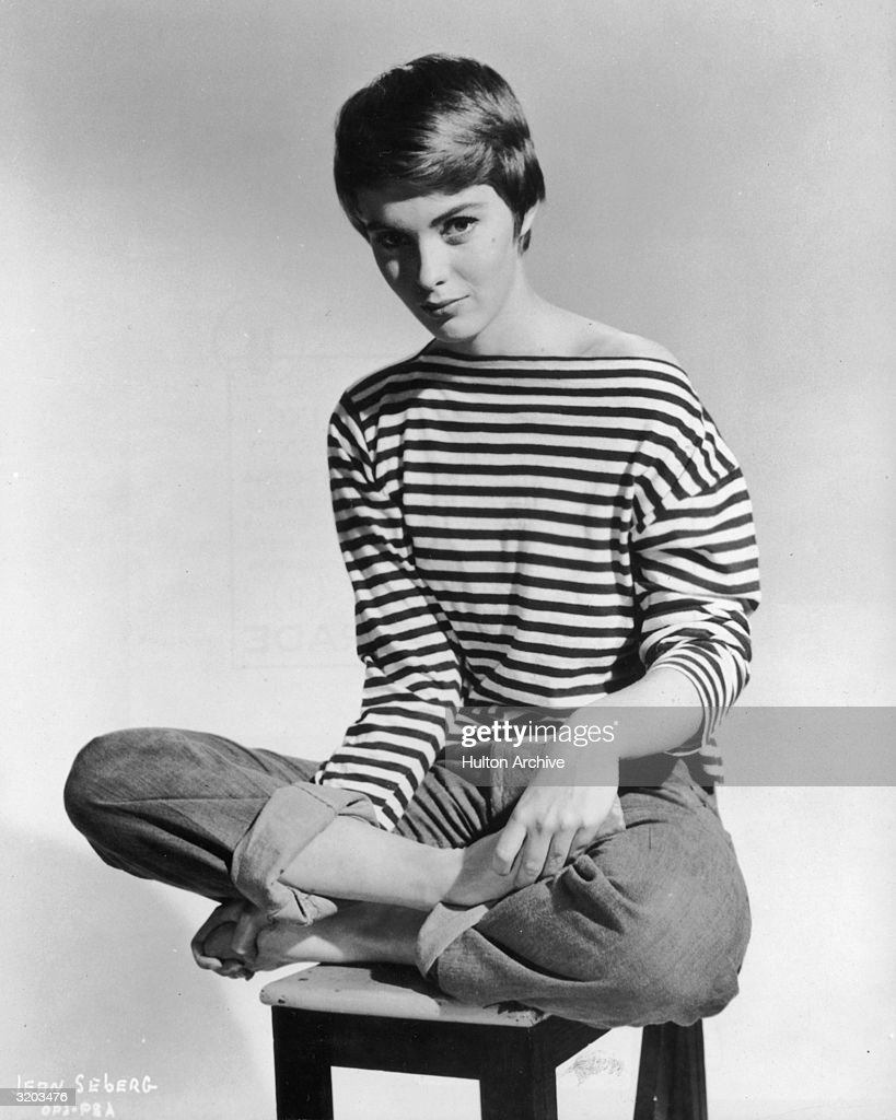 Promotional portrait of American actor Jean Seberg (1938 - 1979) sitting barefoot and cross-legged on a stool, wearing rolled blue jeans and a French-striped sailor jersey pulled off one shoulder.