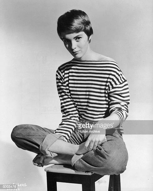 Promotional portrait of American actor Jean Seberg sitting barefoot and crosslegged on a stool wearing rolled blue jeans and a Frenchstriped sailor...
