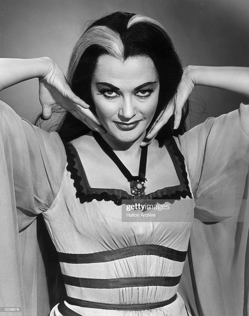 Promotional portrait of Canadian actor Yvonne De Carlo, wearing her costume and makeup from the television series, 'The Munsters'. She holds her hands up to her face.