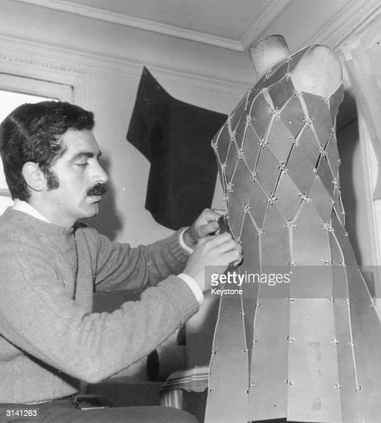 Spanish born dress designer Paco Rabanne at work on one of his metallic dresses