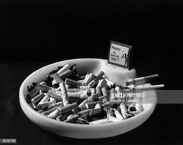 Stilllife of an ashtray containing cigarette butts and a book of matches which reads 'Happy to serve you'