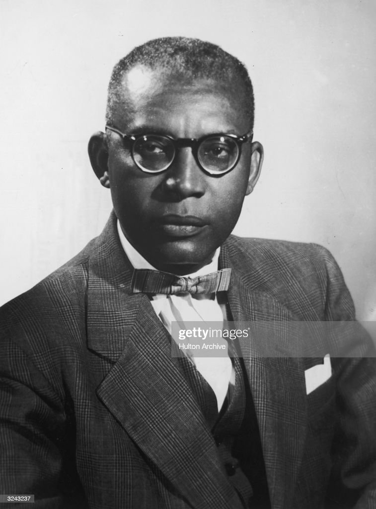 Studio headshot portrait of Haitian president Francois 'Papa Doc' Duvalier (1907-1971) wearing a suit with a bow tie and eyeglasses.
