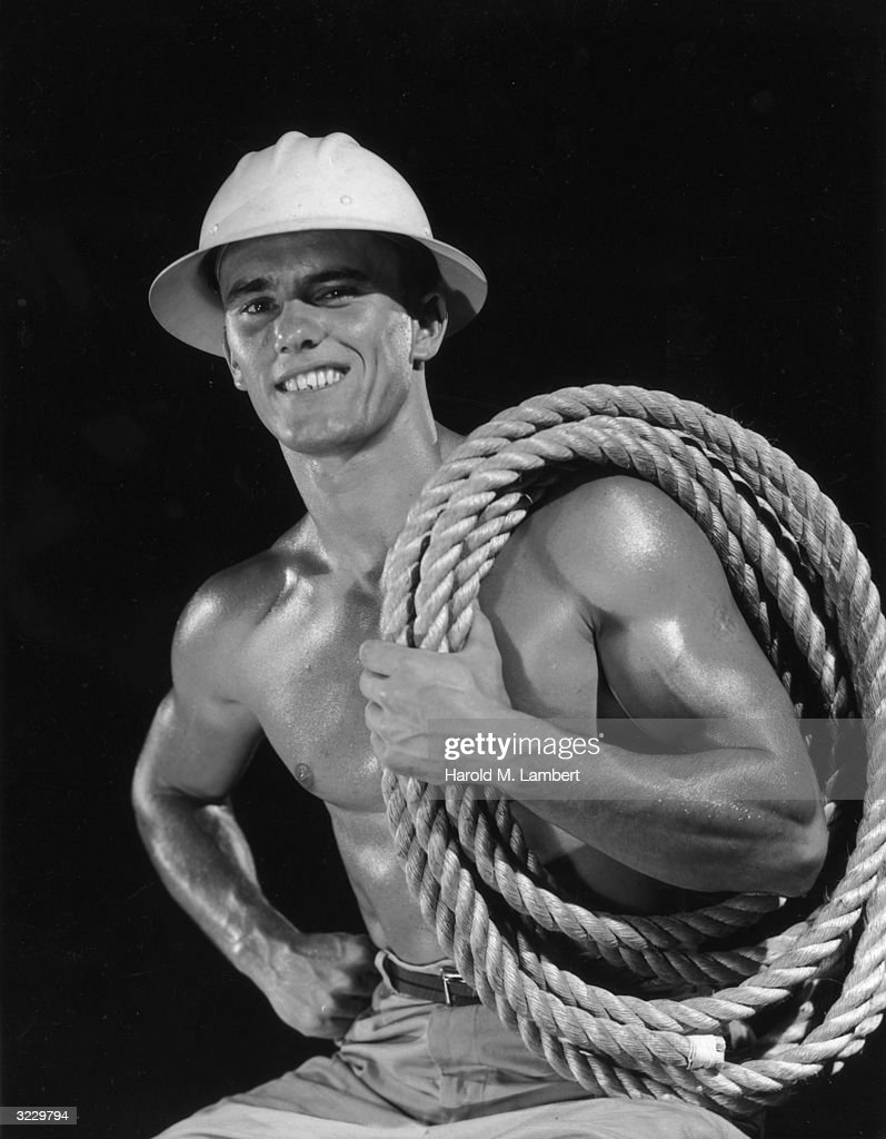 Studio portrait of a barechested construction worker with glistening muscles, wearing a hard hat and holding thick rope coiled over one shoulder.