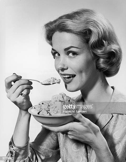 Studio portrait of a blonde woman eating a bowl of ice cream in front of a light backdrop She lifts a spoonful from the bowl