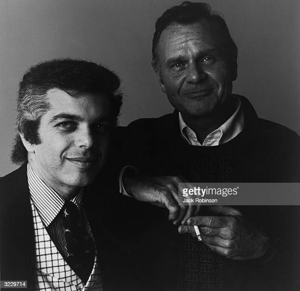 Studio portrait of American fashion designers Ralph Lauren and Bill Blass posing together Blass smokes a cigarette while leaning on Lauren's shoulder