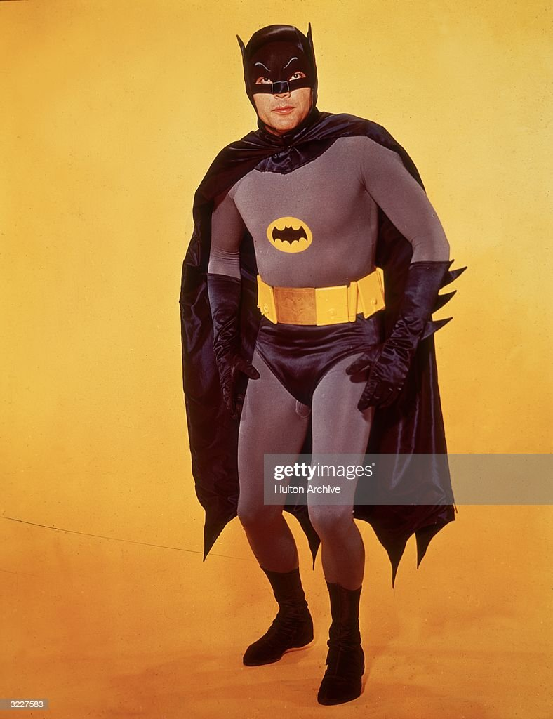 American actor Adam West poses in costume as Batman in front of a yellow backdrop in a promotional portrait for the television series 'Batman'