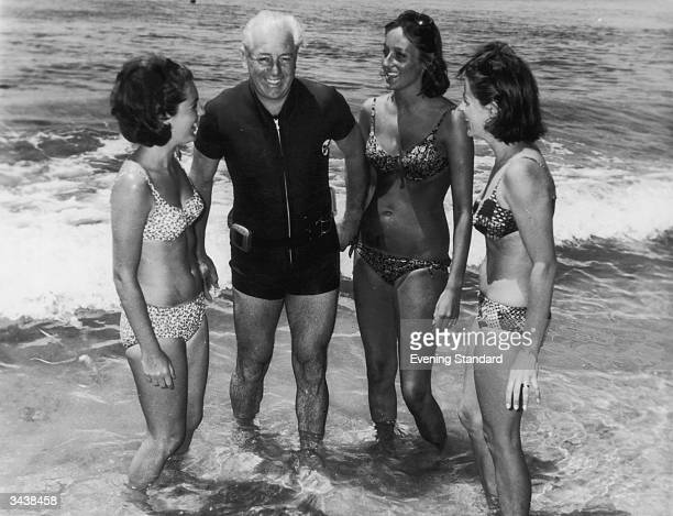Australian prime minister Harold Holt on the beach with three women