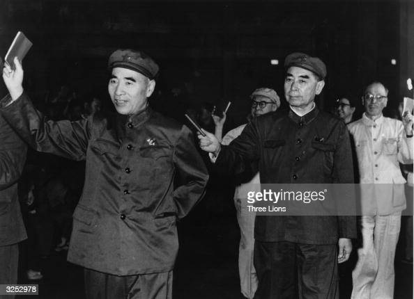 Communist Chinese leaders demonstrate their allegiance to Mao by holding quotations aloft They are in the front row left to right Len Biao president...