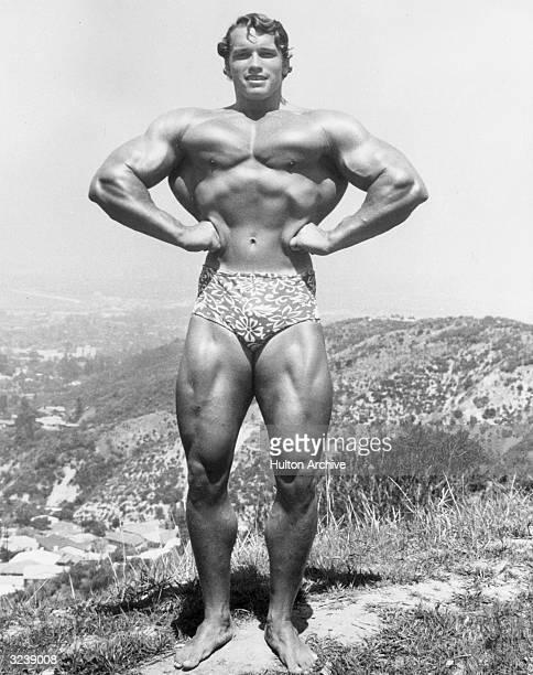 Fulllength image of Austrianborn bodybuilder Arnold Schwarzenegger standing and flexing on top of a hillside near Muscle Beach Santa Monica...