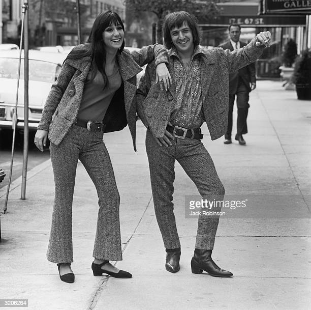 Married American pop/rock singing duo Sonny Bono and Cher lean against an imaginary wall on the sidewalk of East 67th Street New York City They wear...