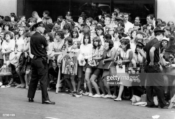 Police keep an eye on a crowd of Beatles fans gathered in the street opposite the hotel in New York where the group are staying in the hope of a...