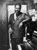 Portrait of American jazz musician Thelonious Monk holding a cigarette standing next to a piano at the Village Gate New York City