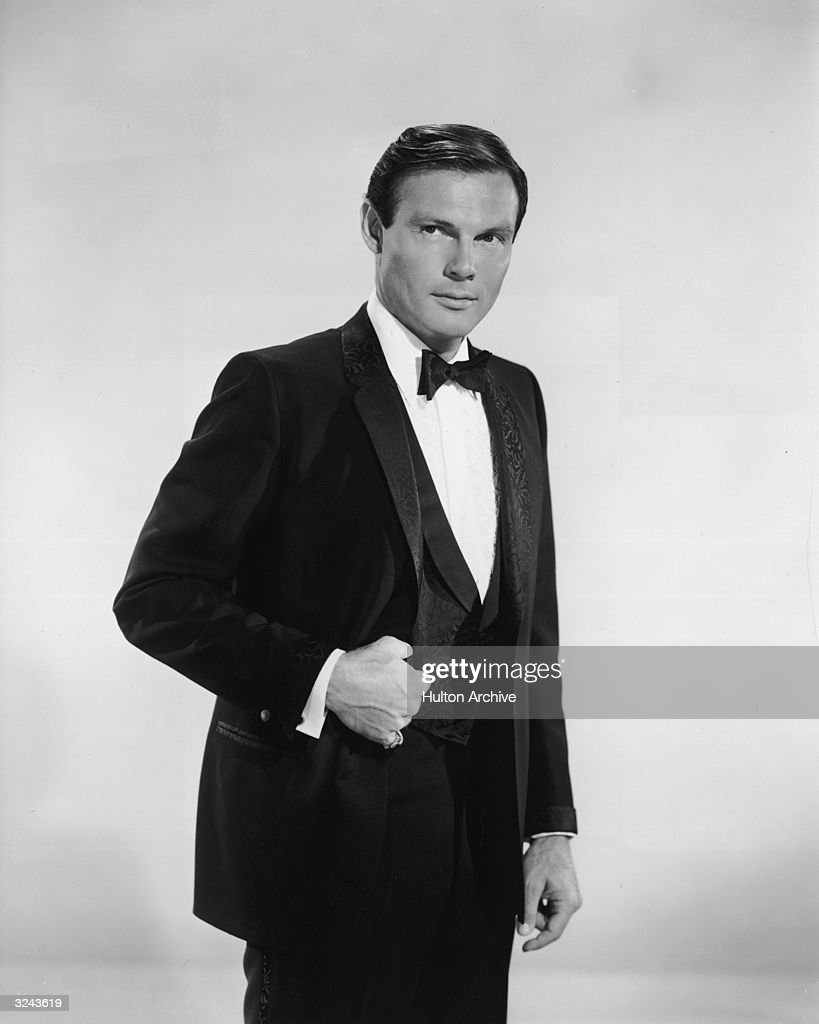 Promotional studio portrait of American actor Adam West, from the television series 'Batman' standing with his thumb in the vest pocket of his tuxedo.