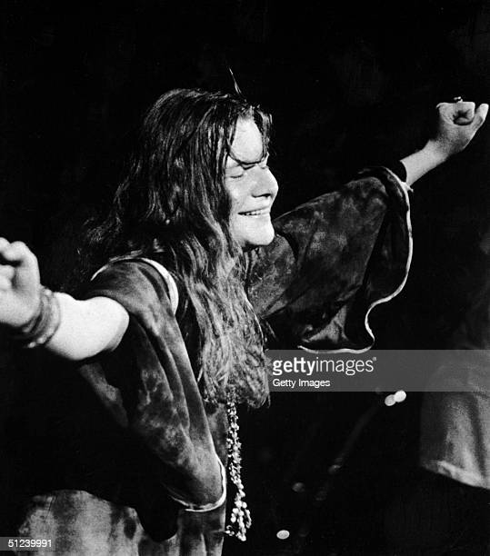 Circa 1967 American singer Janis Joplin closes her eyes and outstretches her arms during a performance late 1960s