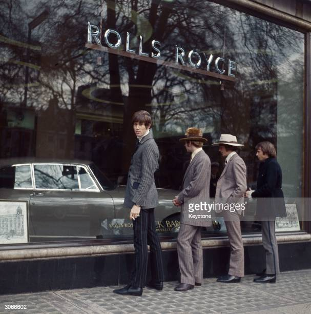 British pop group The Bee Gees formerly The Brothers Gibb gaze through the window of a Rolls Royce showroom