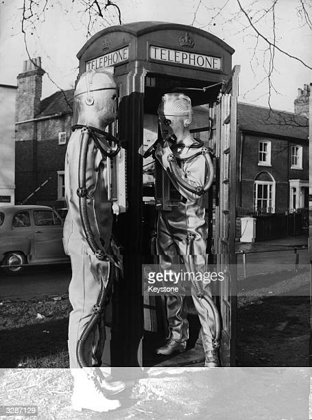 Two actors dressed as Cybermen from the BBC Television programme 'Dr Who And The Moonbase' at a telephone box in London
