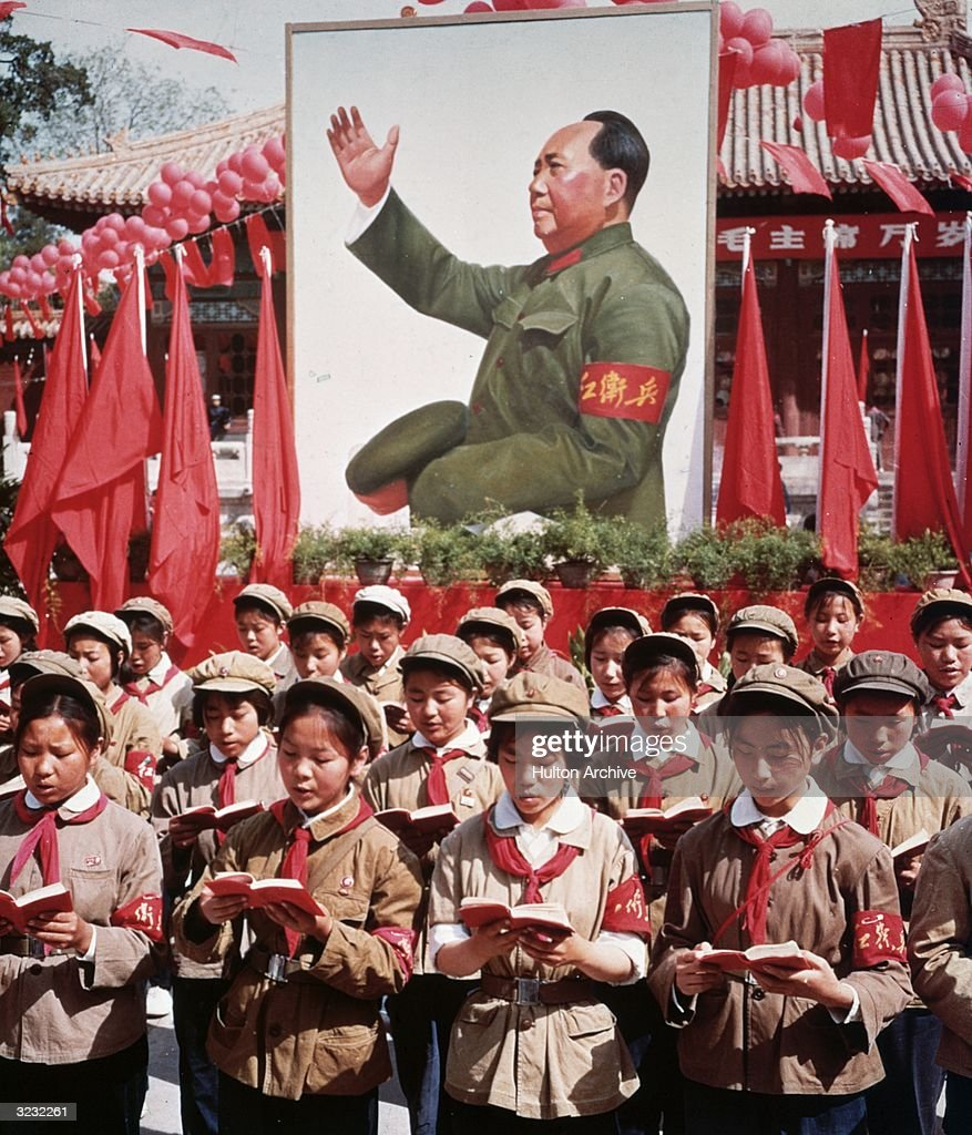 A group of Chinese children in uniform in front of a picture of Chairman Mao Zedong holding Mao's 'Little Red Book' during China's Cultural Revolution