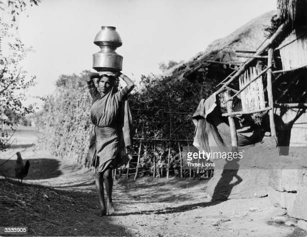 A woman of the Untouchables caste carrying two pots on her head