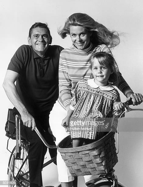 American actors Dick York Elizabeth Montgomery and Erin Murphy pose on a bicycle in a promotional portrait for the television series 'Bewitched'