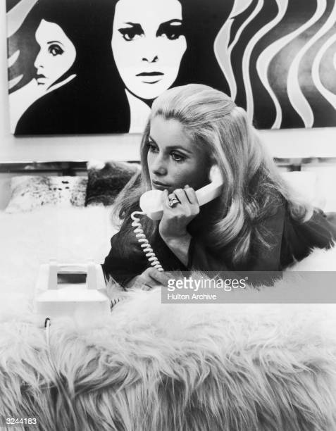 French actor Catherine Deneuve lies on her stomach on a shaggy comforter on top of a bed and holds a telephone receiver up to her ear There is a pop...