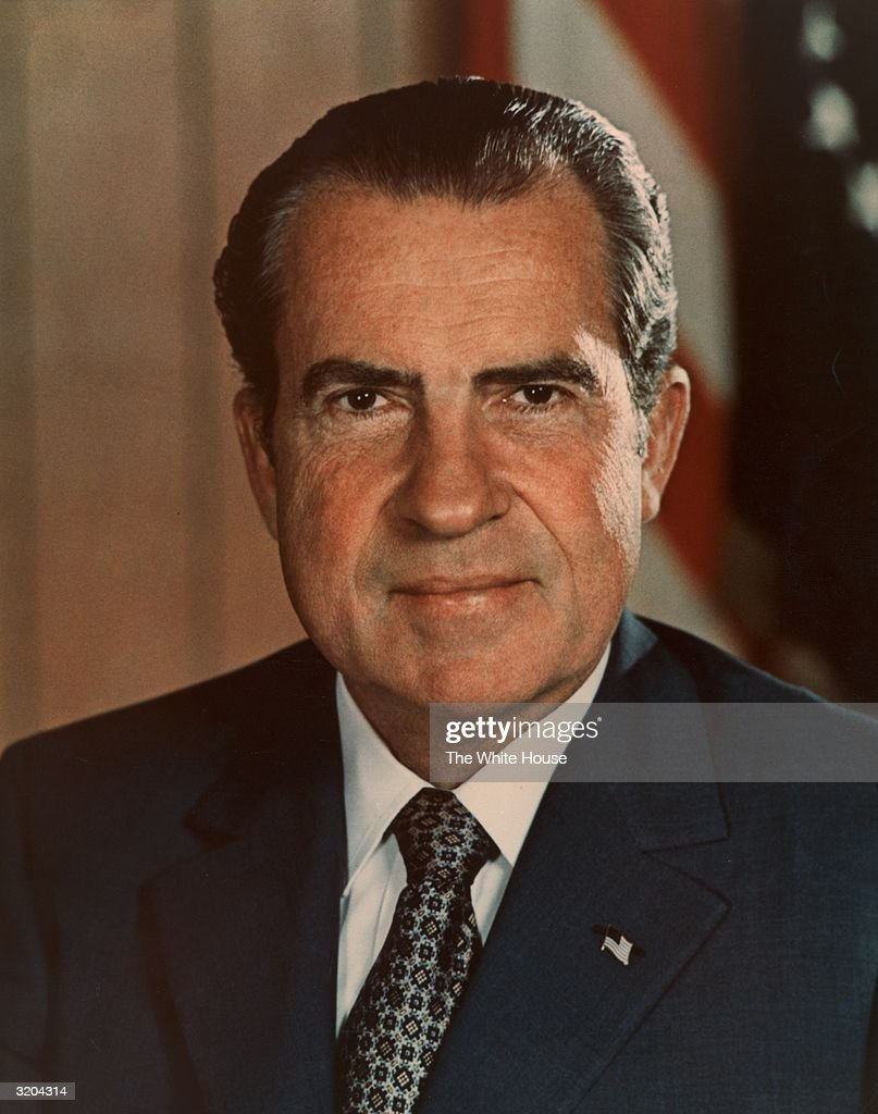 Headshot portrait of 37th American president Richard M. Nixon (1913-1994), wearing a U.S. flag lapel pin, smiling in front of a U.S. flag. Nixon's presidency lasted from 1968 until 1974.