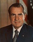 Headshot portrait of 37th American president Richard M Nixon wearing a US flag lapel pin smiling in front of a US flag Nixon's presidency lasted from...