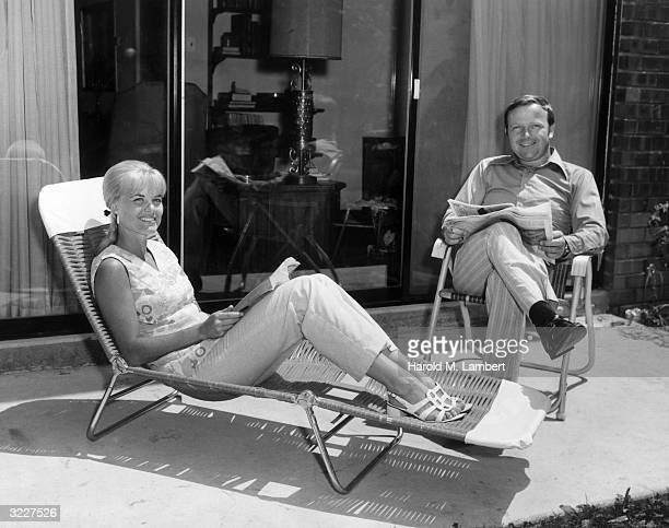 Portrait of a couple smiling as they sit in lawn chairs on their backyard patio The man sits with a newspaper while the woman reclines with a book