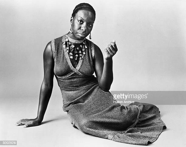 Studio portrait of American pianist and jazz singer Nina Simone reclining on the floor while wearing a sleeveless Vneck dress with a shell neckpiece
